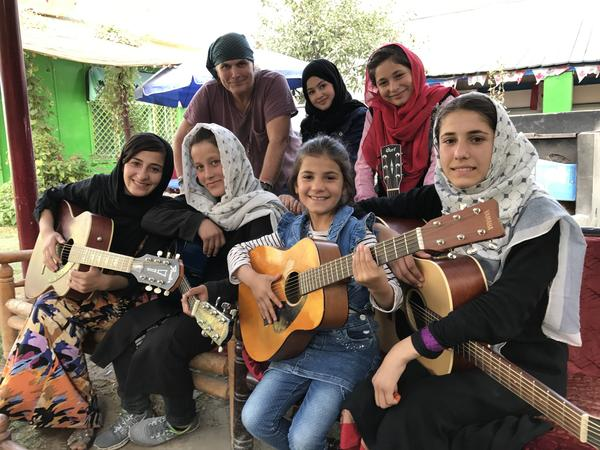 "The Miraculous Love Kids music school founder Lanny Cordola (top left) stands with Madina Mohammadi (top center), Mursal (top right) and other students outside their rehearsal space in Kabul. Their favorite song is ""Fragile"" by Sting. ""What we're trying to do with music is not singing and dancing and fancy stuff,"" Cordola says. ""You know, these are songs of compassion and hope and healing."""