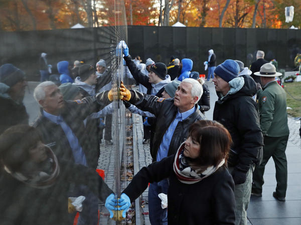 Vice President Mike Pence, with his wife Karen Pence, and Interior Secretary Ryan Zinke clean a portion of the wall at the Vietnam Veterans Memorial on Veterans Day, Saturday, Nov. 11.