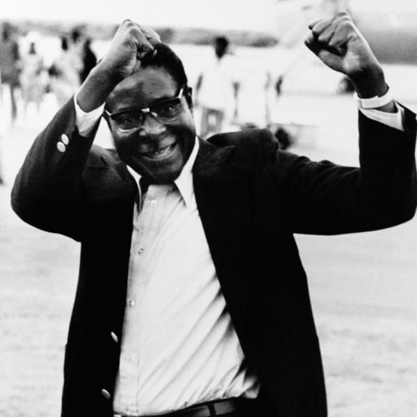 Robert Mugabe raises his fists in salute to a group of supporters as he arrives at Lusaka Airport, Zambia, to attend an African leaders' summit conference in January 1977.