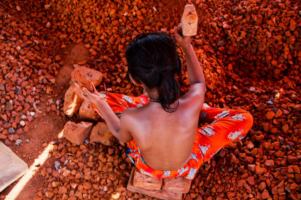 A Bangladeshi child works in a brick-breaking yard in Dhaka, Bangladesh. The broken bricks are mixed in with concrete. Typically working barefoot and with rough utensils, a child worker earns less than $2 a day.