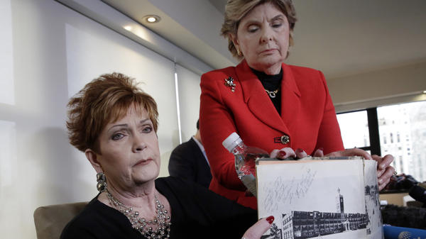 Beverly Young Nelson (left), who has accused Alabama Republican Roy Moore of sexual misconduct, and her attorney Gloria Allred hold Nelson's high school yearbook that Nelson says was signed by Moore. Nelson now says she added notes to the inscription.
