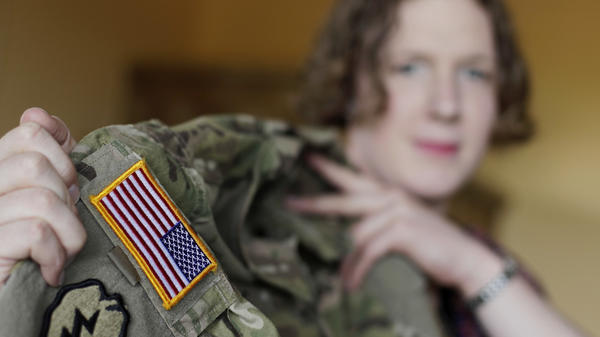 Transgender U.S. Army Capt. Jennifer Sims lifts her uniform during a July interview with The Associated Press in Beratzhausen near Regensburg, Germany.