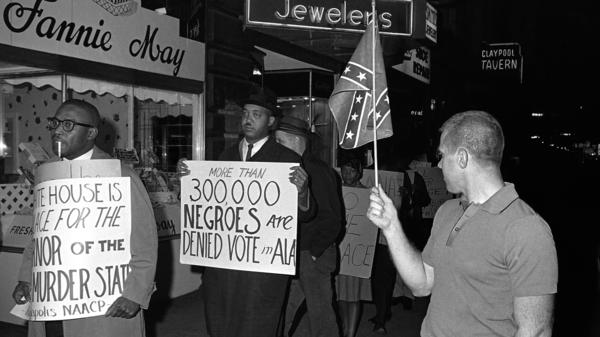"A demonstrator carries a sign that says ""More than 300,000 Negroes are Denied Vote in Ala"" to protest then-Alabama Gov. George Wallace's visit to Indianapolis in 1964. The word ""Negro"" was widely used to describe black people in the U.S. during the early civil rights era."