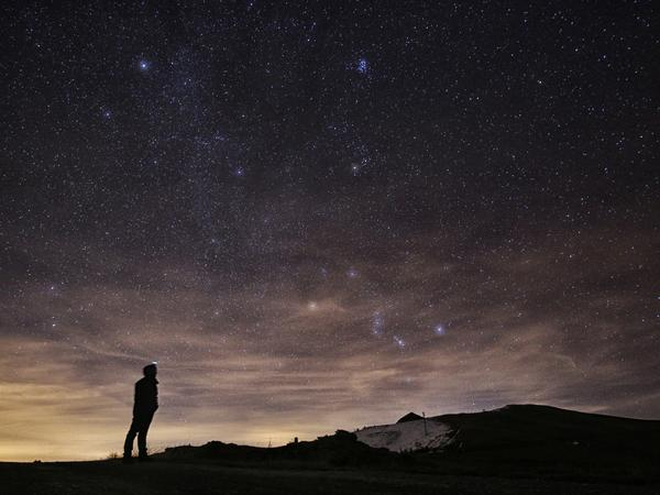 A photographer looks at the night sky to see the annual Geminid meteor shower in northern Italy in December 2015. This year's shower coincides with a close-range visit by its parent asteroid.
