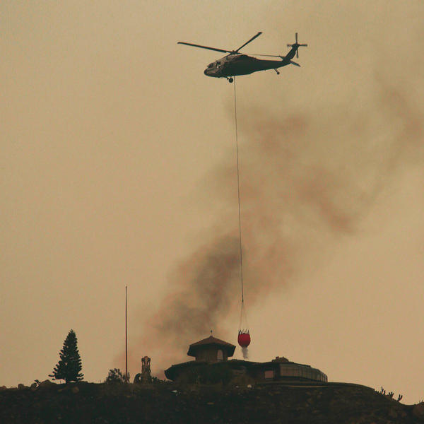 In this photo provided by the Santa Barbara County Fire Department, a helicopter makes a water drop near a house that was not on fire on a hill above Bella Vista Drive in Montecito, Calif.