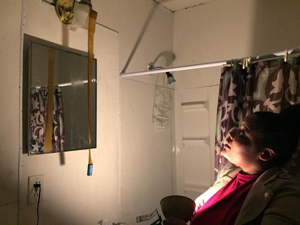 Christine Thompson uses a handheld light to show some water damage in her bathroom.  She says the overhead light only goes on when the shower is turned on.