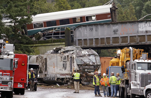 Cars from an Amtrak train lie spilled onto Interstate 5 below as some train cars remain on the tracks above on Monday in DuPont, Wash.