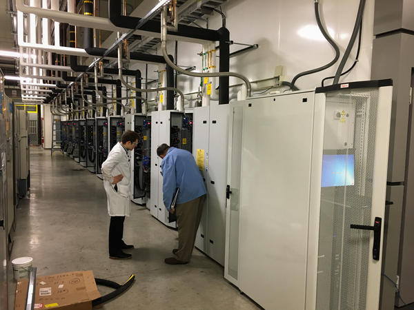 Technicians examine part of a 74-foot-long freezer. Robots inside the freezer will handle millions of specimens and store them in even colder freezers inside.