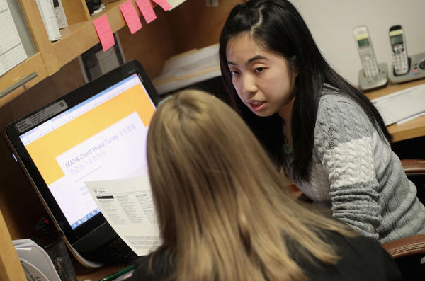 Kelley Mui helps a client sign up for health insurance through the Affordable Care Act on Dec. 15 at the Midwest Asian Health Association in Chicago.