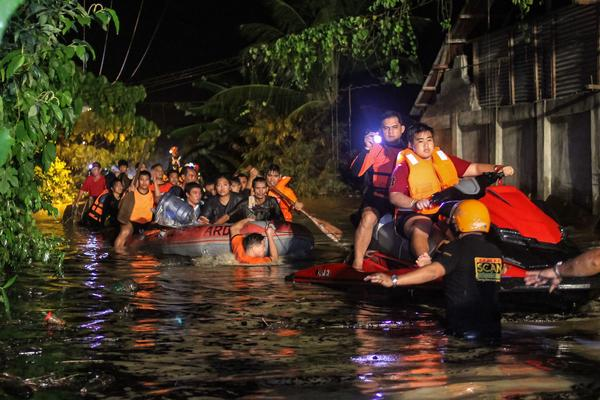 Rescue workers evacuate flood-affected residents in Davao on the southern Philippine island of Mindanao early on Saturday, after Tropical Storm Tembin dumped torrential rains across the island.