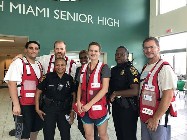 Nineteen-year-old Andrew Enos (left) managed a shelter for Hurricane Irma evacuees in Florida at North Miami Senior High School in September. Here he stands with other American Red Cross volunteers and first responders. From left to right: Andrew Enos, Brian Michaud, Officer Buissereth, Detective Charley, Jillian Birchmeier, Sergeant Horn and Bill Bloodgood. (Courtesy Andrew Enos)