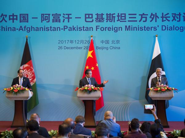 China's Foreign Minister Wang Yi (center), Afghanistan's Foreign Minister Salahuddin Rabbani (left) and Pakistan's Foreign Minister Khawaja Muhammad Asif (right) speak after the first China-Afghanistan-Pakistan Foreign Ministers' Dialogue in Beijing on Dec. 26.