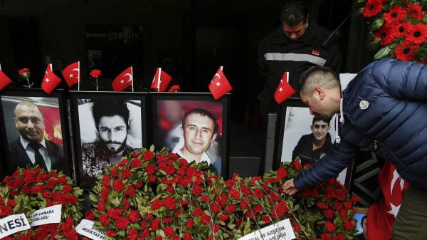 A man leaves a carnation outside Reina nightclub as people have gathered to remember the victims of a deadly New Year's attack a year ago, in Istanbul.