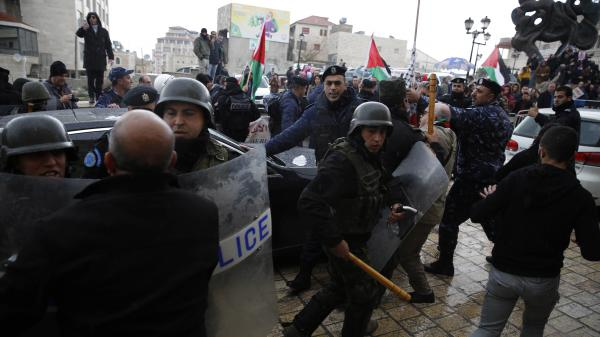 Palestinian security forces push away demonstrators from the convoy of Greek Orthodox Patriarch of Jerusalem Theophilos III, during a protest against his visit to the Church of the Nativity in the West Bank city of Bethlehem on Saturday.