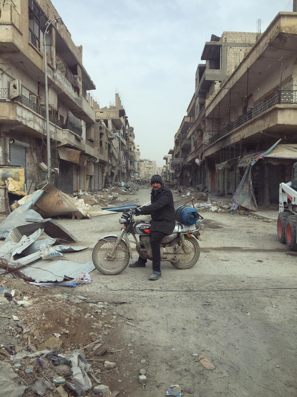 A man rides through Raqqa, Syria, on his motorbike.