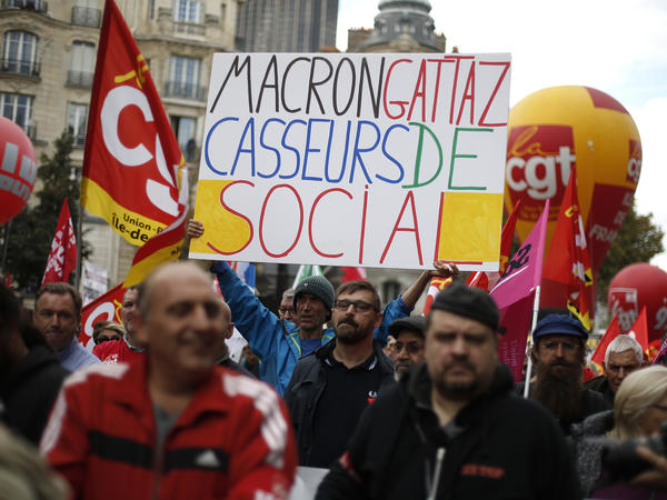 """Protesters hold a banner saying, """"Macron and Gattaz, breakers of the social safety net,"""" which refers to President Macron and Pierre Gattaz, leader of a French business association."""