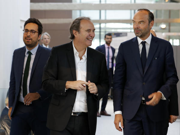 Xavier Niel, center, speaks with French Prime Minister Edouard Philippe and Minister for the Digital Sector Mounir Mahjoubi, left, as they visit the startup incubator Station F in Paris on Aug. 31.