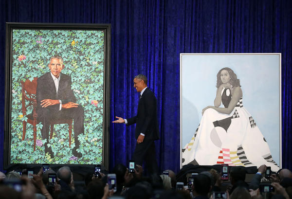 "Obama stands between the portraits. His will be permanently installed in the ""America's Presidents"" exhibit at the National Portrait Gallery in Washington, D.C."