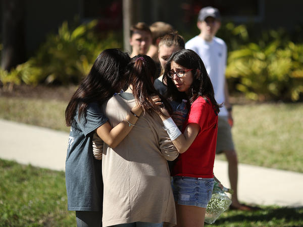 Students of Marjory Stoneman Douglas High School gather on Thursday in Parkland, Fla. Fourteen students and three staff members were killed in a shooting at the school on Wednesday.
