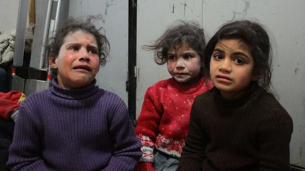 Syrian children caked with the dust of bombed buildings await care at a makeshift hospital in eastern Ghouta on Friday.