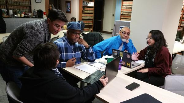 Former juvenile-lifers Johnny Alexander (left, in cap) and Edward Sanders, second from right, work with staff and students to learn how to check their credit scores at a workshop run by Michigan's State Appellate Defenders Office or SADO.