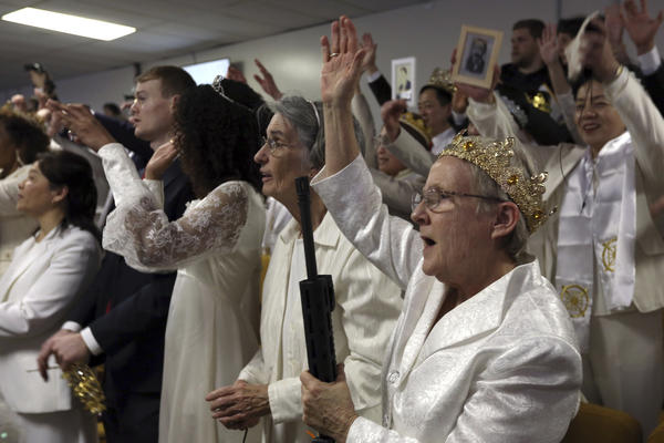 A woman wears a crown and holds an unloaded weapon during services at the World Peace and Unification Sanctuary on Wednesday in Newfoundland, Pa.