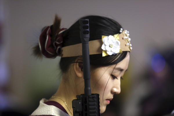 "A woman holds an unloaded weapon during the service. ""We pray they would stand as kings and queens with their crown and rod of iron,"" the Rev. Hyung Jin ""Sean"" Moon said."