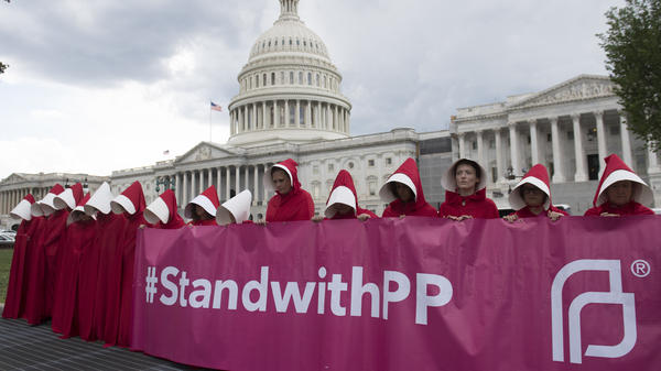 Supporters of Planned Parenthood dressed as characters from <em>The Handmaid's Tale</em> protest last June outside the Capitol against Senate Republicans' health care bill.