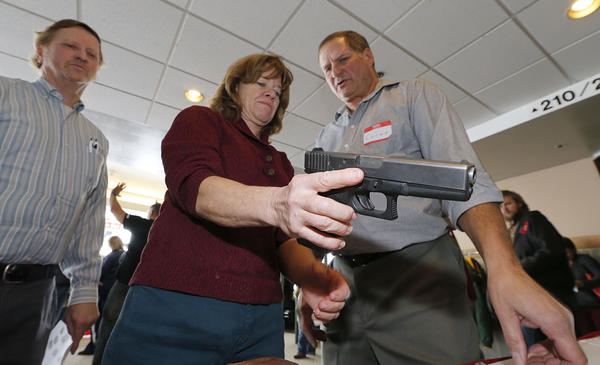 A Utah teacher is shown how to handle a handgun by instructor Clint Simon (right) at a concealed-weapons training class to 200 Utah teachers in 2012.