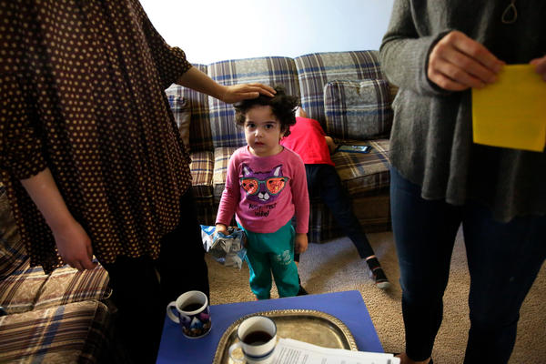 Fields (right) visits with Asmaa Dawoud, a refugee from Syria, while her daughter Dana looks on.