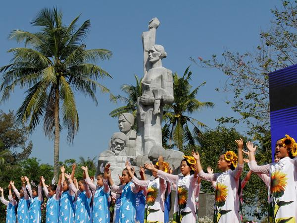 Children perform at a war memorial dedicated to the victims of the My Lai massacre in the village of Son My during a ceremony marking the 50th anniversary of the massacre on March 16, 2018.