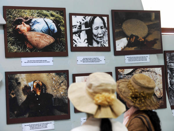 Two young women look at photographs showing massacre scenes as they tour the My Lai Massacre Museum at My Lai village in the central province of Quang Ngai.