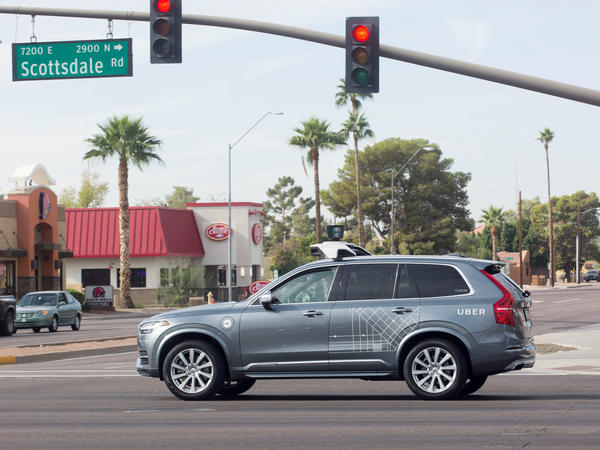 A self-driving Uber moves through an intersection in Scottsdale, Ariz., on Dec. 1, 2017. Uber on Monday suspended its self-driving tests in four cities after a pedestrian was killed by an autonomous Uber vehicle in Tempe, Ariz.