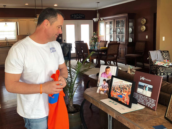 Scott Cosner, the father of twin 15-year-old boys who were both injured in the Marshall County High School shooting, holds a shirt another Kentucky high school made to commemorate the shooting. He says guns aren't the problem.