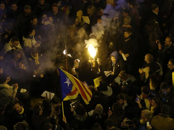 Portesters burn a photo of Spain's Prime Minister Mariano Rajoy during a protest over the jailing of Catalan politicians in Barcelona on Friday.