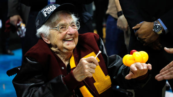 Sister Jean Dolores Schmidt, 98, longtime men's basketball team chaplain, holds a piece of net as she celebrates Loyola's win sending the team to the Final Four.