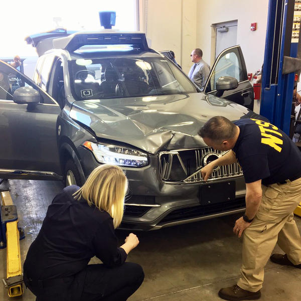 A photo provided by the National Transportation Safety Board shows investigators examining the self-driving Uber SUV that fatally struck a woman in Tempe, Ariz., this month.