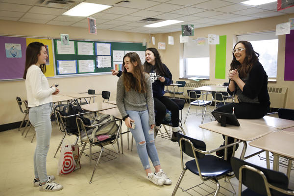 Students in Kara Cisco's civics class chat with her about their assignment after class.