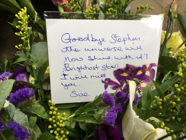 Flowers and a note honor the renowned theoretical physicist near the university church of St. Mary the Great in Cambridge, where a private funeral service was held Saturday.