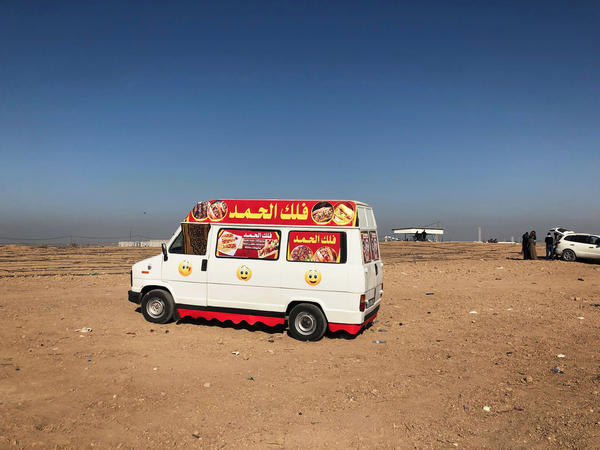 A food truck is parked several hundred yards back from the border fence.
