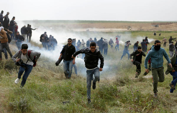 Palestinian protesters flee from tear gas during clashes near the border with Israel east of Gaza City during a demonstration on March 30.