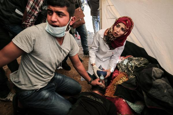 Medical staff help an injured Palestinian man at an emergency medical tent after clashes with Israeli security forces following a demonstration near the border with Israel in the southern Gaza Strip, on April 1.