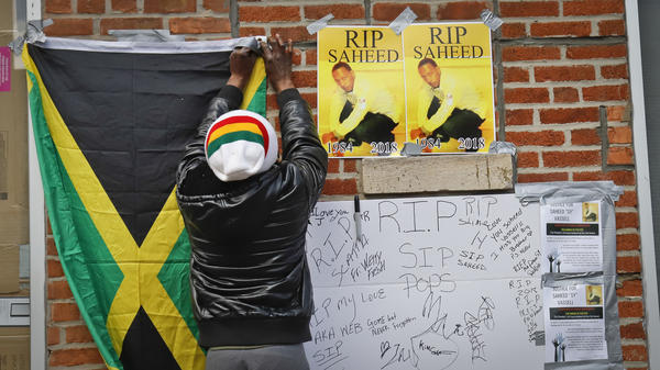 A resident pins the Jamaican national flag at a makeshift community memorial for Saheed Vassell on Thursday.