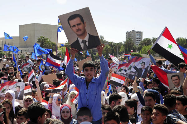 A crowd in central Damascus waves flags and portraits in support of President Bashar Assad on Monday, two days after the U.S., Britain and France carried out airstrikes. The photo was released by the official Syrian news agency SANA.