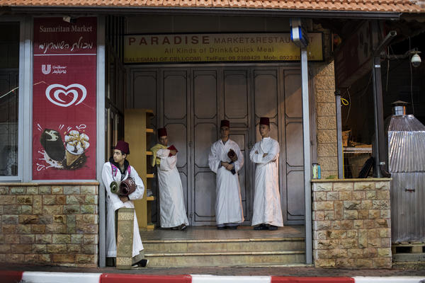 Young Samaritans wait outside a grocery across the street from the Samaritan synagogue on Mount Gerizim. Samaritans straddle the political divide: Half live as Israelis in one small Samaritan neighborhood. The other half live as Palestinians on their holy mountain in the West Bank.