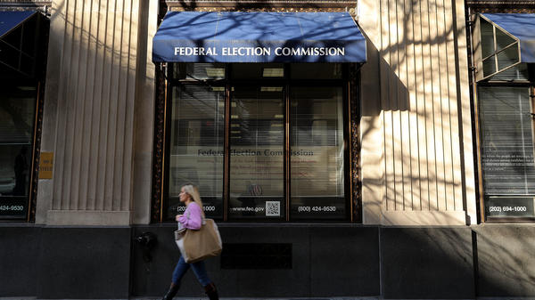 A pedestrian walks past the Federal Election Commission's headquarters October 24, 2016 in Washington, DC.