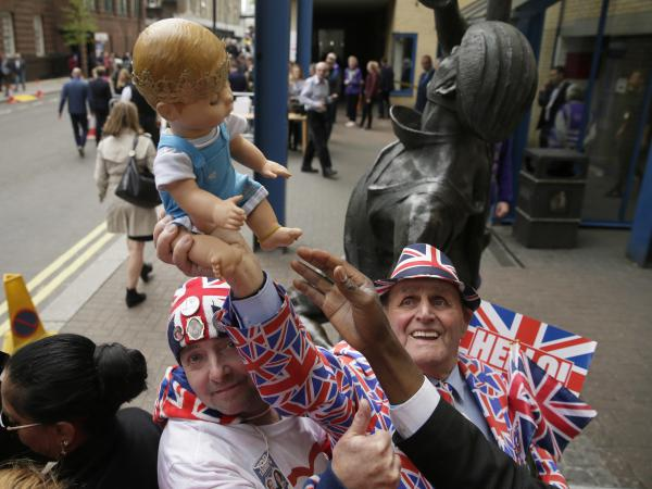 Royal fans pose holding a doll outside of St Mary's Hospital in London on Monday. Kensington Palace says the Duchess of Cambridge has given birth to her third child and second son.
