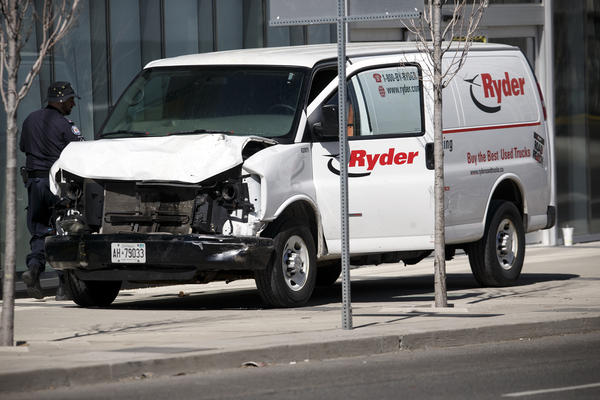 Police inspect a van suspected of being involved in a collision that killed at least 10 people and injured 15 others in Toronto on Monday.