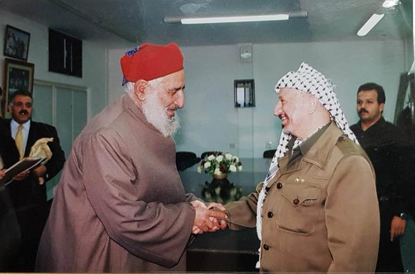 Samaritan priest Saloum Cohen greets Palestinian leader Yasser Arafat in 1998. After the theft, Arafat vowed to root out those responsible.