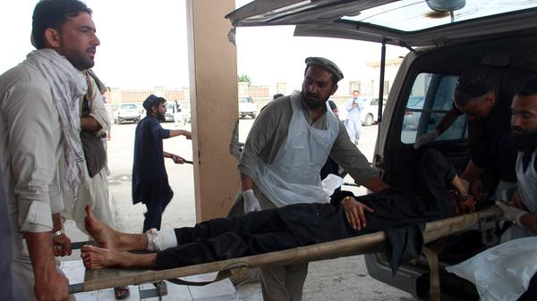 An Afghan man lays on a stretcher as others rush him to a hospital following blast at a mosque being used as a voter registration center in Khost Province on Sunday.